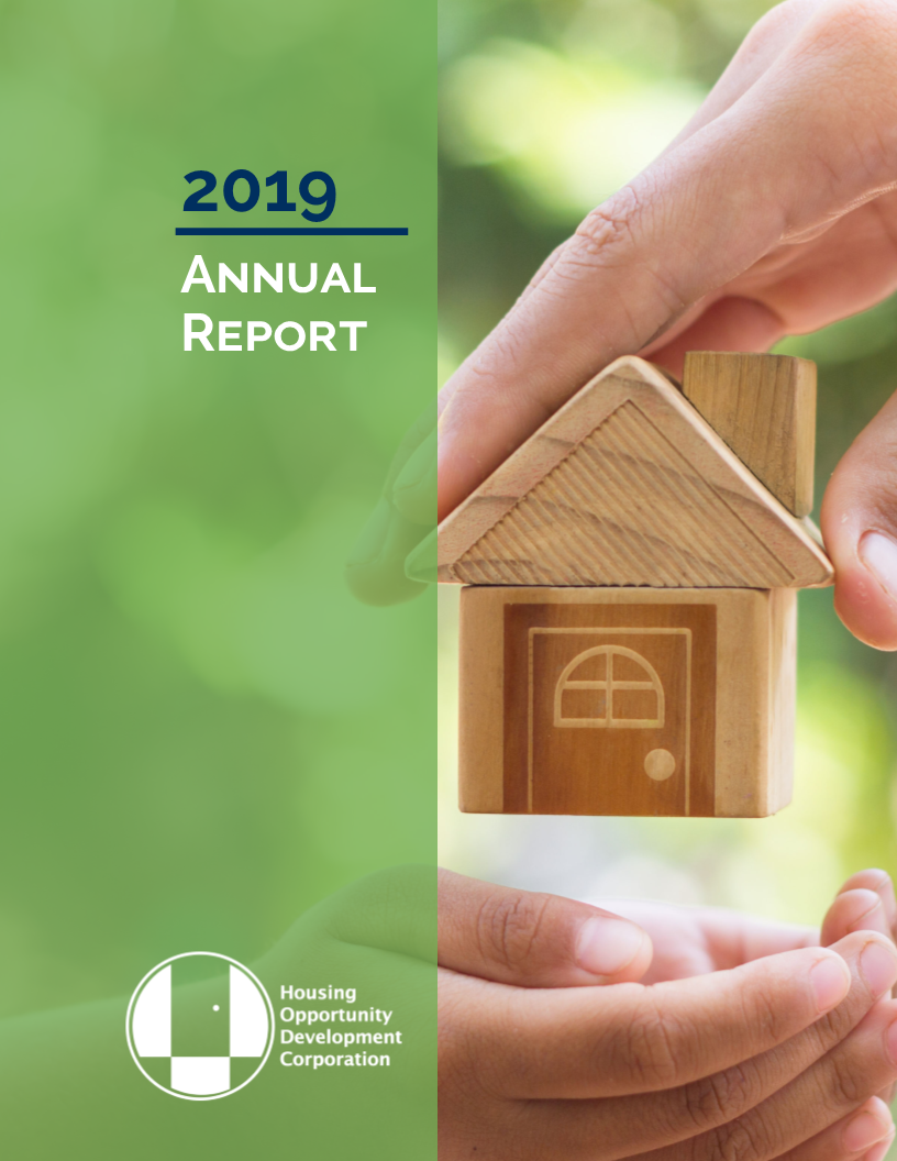 2019 HODC Annual Report cover. Adult hand placing small wooden house in child's hands. Green bar on left with title of HODC 2019 Annual Report and HODC logo.