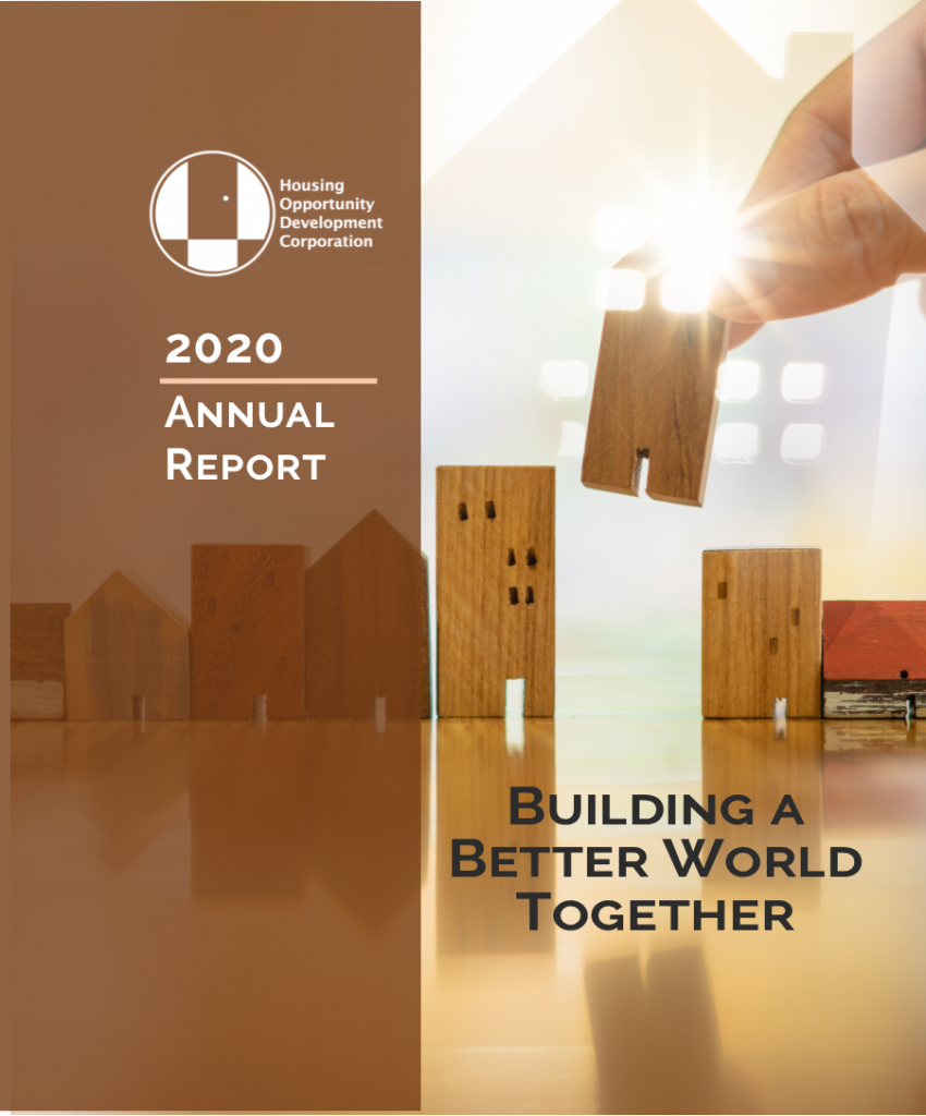"""2020 Annual Report """"Building a Better World Together"""" hand adding wooden building block between other building blocks. A bright light shines through spaces in the building block."""