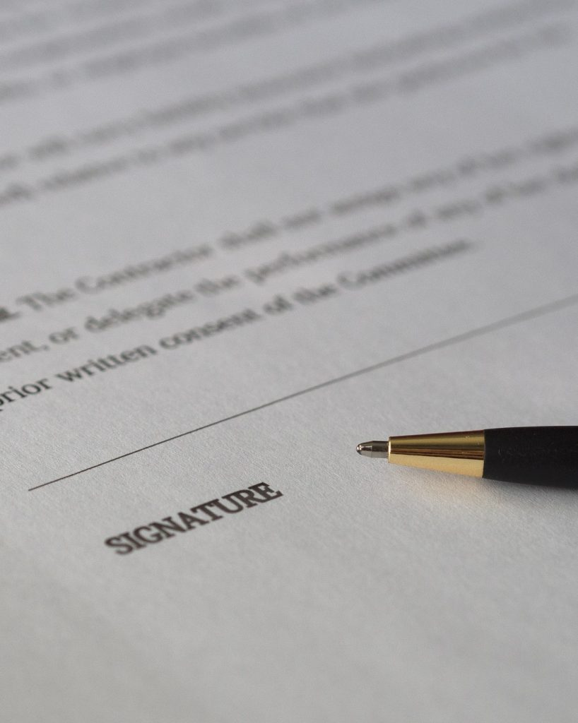A black pen with a gold tip sits on a legal document next to the word Signature.